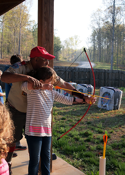A young girl learns to shoot archery