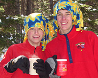 Two Scouts bundled up with warm drinks in their hands